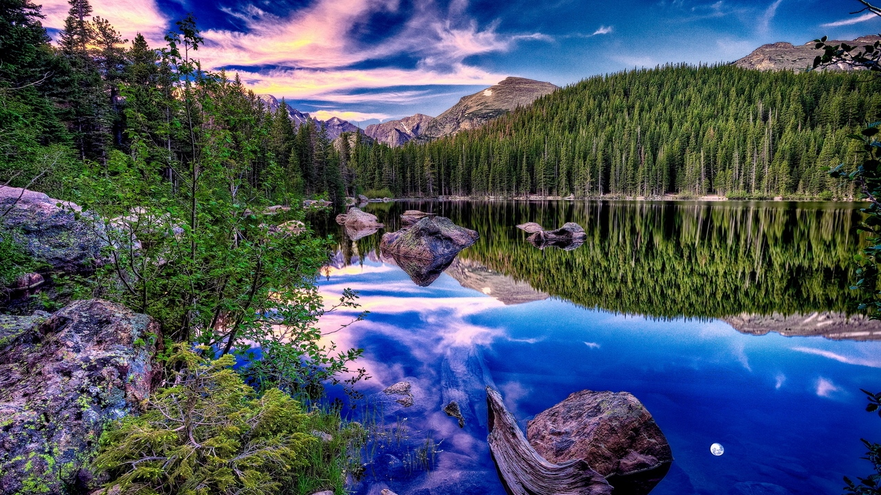 Preview wallpaper brightly, clouds, coast, contrast, lake, mirror, mountains, reflection, sky, snag, stones, wood