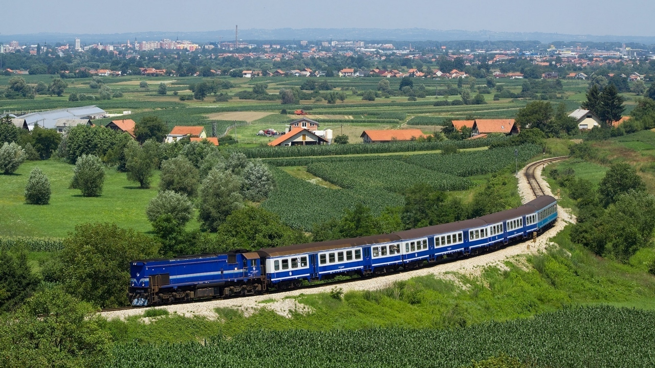 Preview wallpaper city, dark blue, distance, fields, from above, railway, structure, suburb, summer, train, trees
